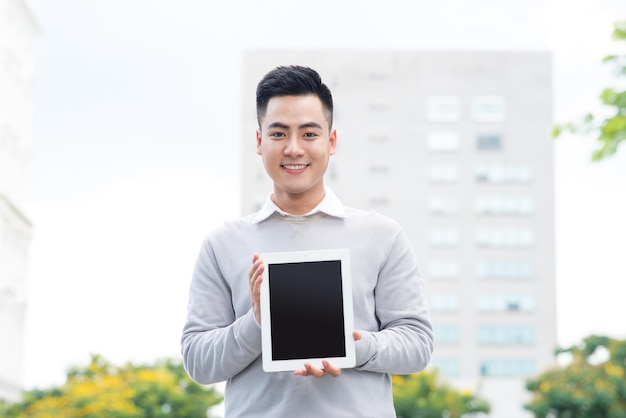 Young business man holding and showing the screen of tablet