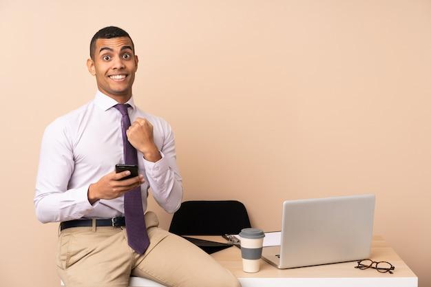 勝利を祝ってオフィスで若いビジネスマン