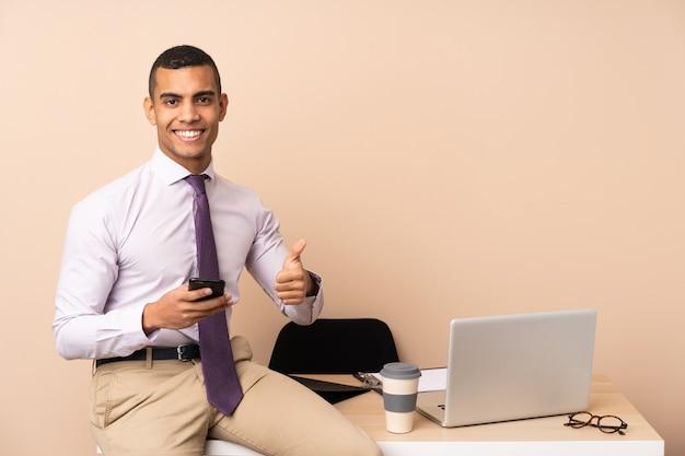 Молодой деловой человек в офисе, давая пальцы вверх жест
