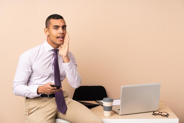何かをささやくオフィスで若いビジネスマン