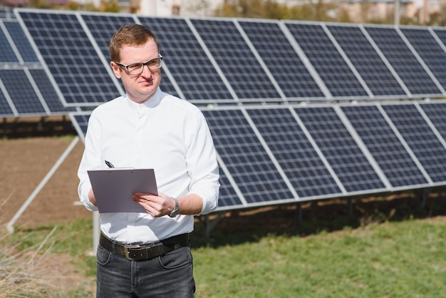 発電所にソーラーパネルの近くの白いシャツの若いビジネスマン