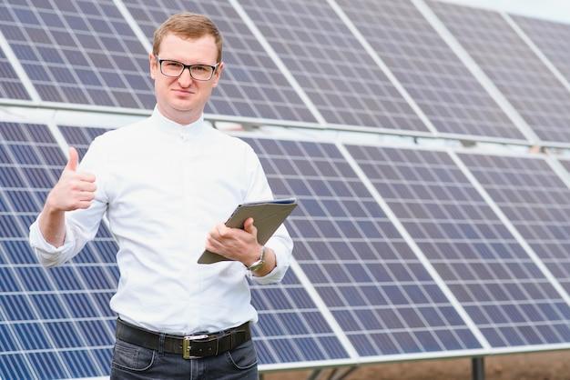 Молодой деловой человек в белой рубашке возле солнечных батарей для электростанций