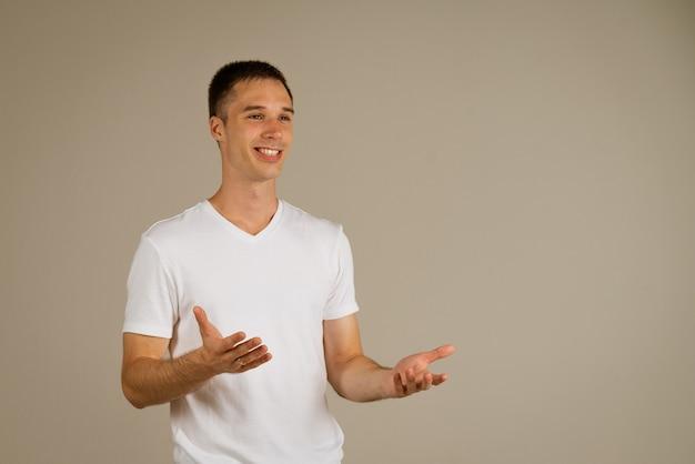 가벼운 벽에 그의 손으로 몸짓 흰색 Tshirt에서 젊은 사업가 프리미엄 사진