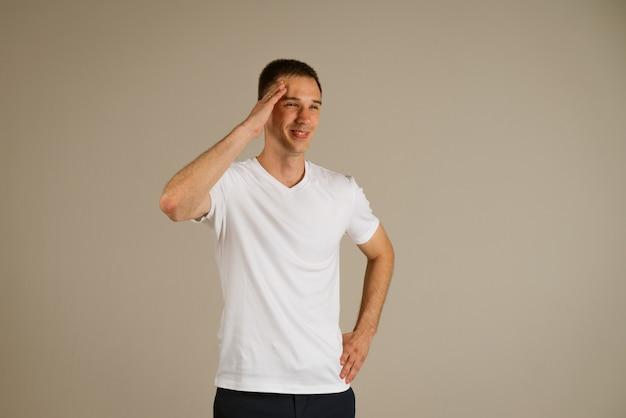 가벼운 벽에 그의 손으로 몸짓 흰색 tshirt에서 젊은 사업가