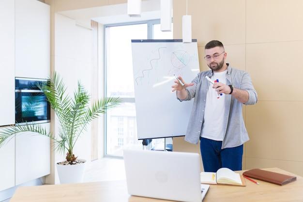 Молодой деловой человек в повседневной одежде, онлайн-встреча, презентация или обучение, с использованием веб-камеры ноутбука и флипчарта с маркерами