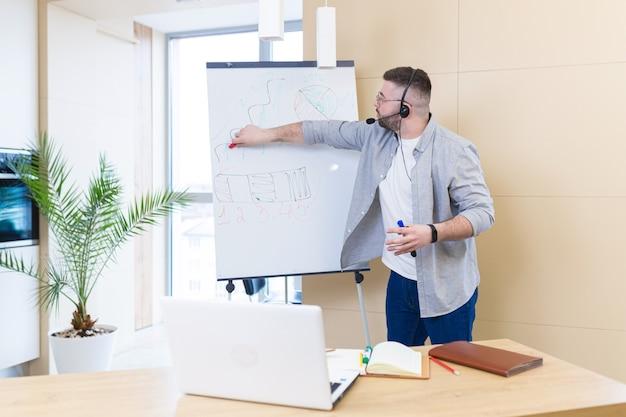 Молодой деловой человек в повседневной одежде, носящий гарнитуру, онлайн-встреча, презентация или обучение, с использованием веб-камеры ноутбука и флипчарта