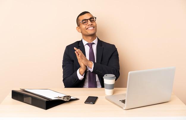 Молодой бизнесмен в своем офисе с ноутбуком и другими документами аплодируют после презентации в конференции