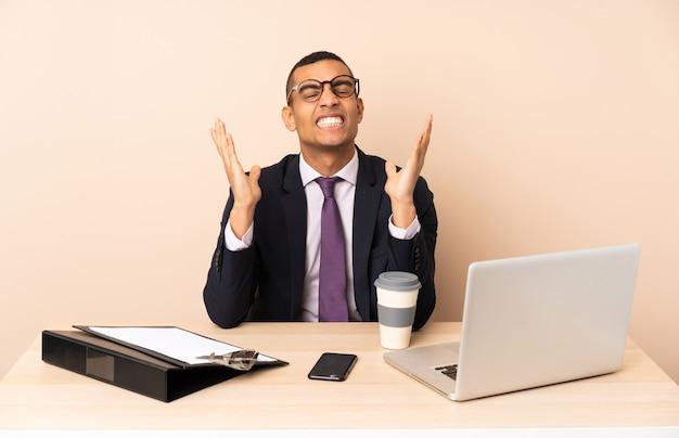 ノートパソコンと悪い状況にイライラした他のドキュメントと彼のオフィスで若いビジネスマン