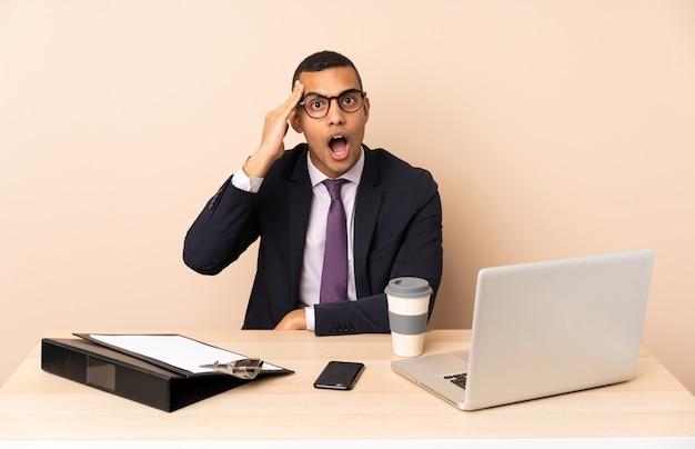 彼のオフィスでラップトップやその他のドキュメントを手にした若いビジネスマンは、何かを実現したばかりで、解決策を意図している