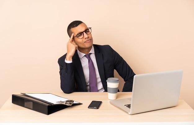 ノートパソコンと疑問や思考を持っている他のドキュメントと彼のオフィスで若いビジネスマン