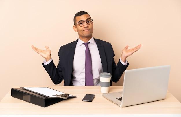 ノートパソコンと手を上げている間疑問を持つ他のドキュメントと彼のオフィスで若いビジネスマン