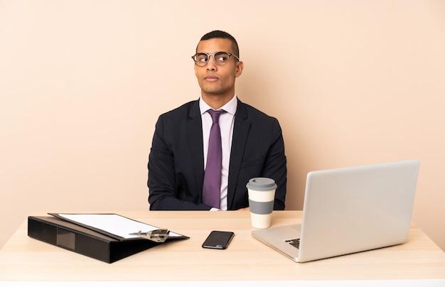 ラップトップと疑いジェスチャー側を探して他のドキュメントと彼のオフィスで若いビジネスマン