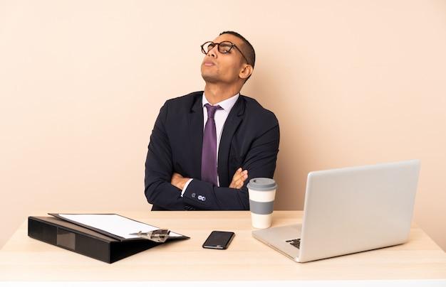 ノートパソコンと他のドキュメントの彼のオフィスで若いビジネスマン