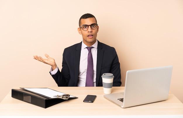 ラップトップと疑問ジェスチャーを作る他のドキュメントと彼のオフィスで若いビジネスマン