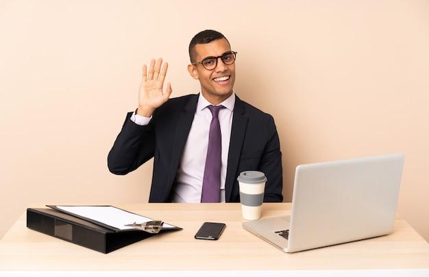 Молодой деловой человек в своем офисе с ноутбуком и другими документами, салютов с рукой с счастливым выражением