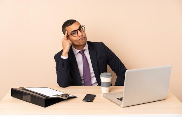 ノートパソコンとアイデアを考えている他のドキュメントと彼のオフィスで若いビジネスマン