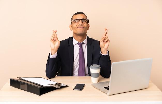 Молодой деловой человек в своем офисе с ноутбуком и другие документы с пальцами скрещивания и желая лучшего
