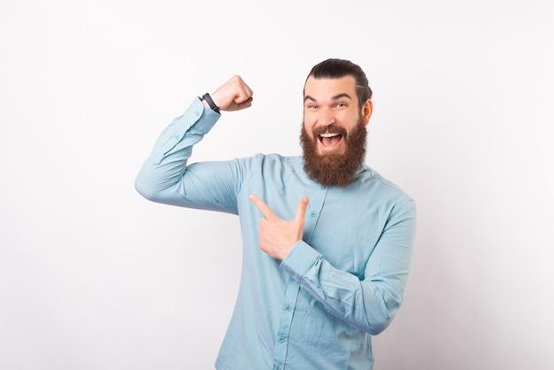 若いビジネスマンは上腕二頭筋を指差しながら腕を上げています。