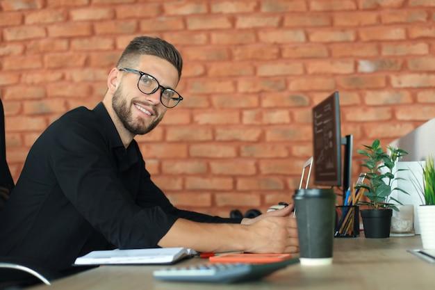 Молодой деловой человек использует ноутбук, сидя в офисе, глядя на камеру, улыбаясь.