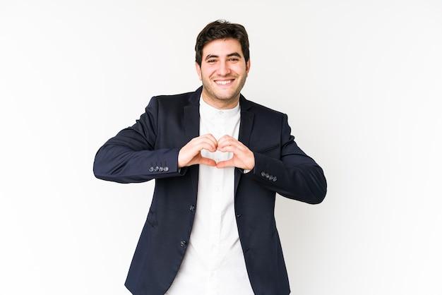 白い笑顔で孤立し、手でハートの形を示す若いビジネスマン。