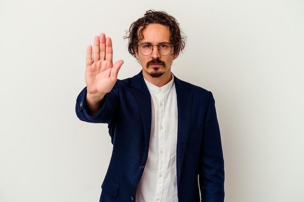 若いビジネスマンは、一時停止の標識を示している手を伸ばして白い立って孤立し、あなたを妨げています。