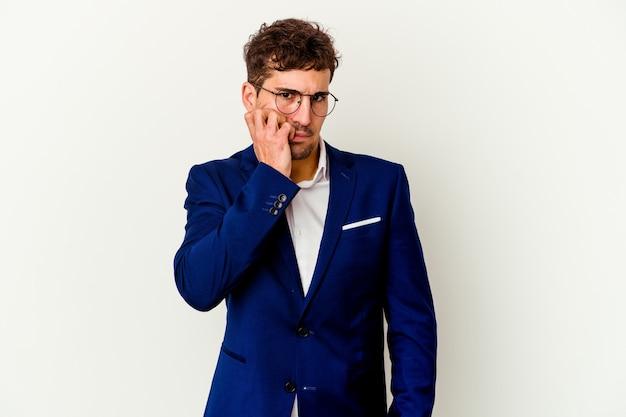 指の爪を噛む白い壁に孤立した若いビジネスマン、神経質で非常に心配