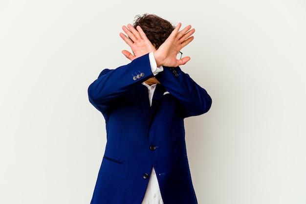 Молодой деловой человек изолирован на белой стене, скрестив две руки, концепция отрицания