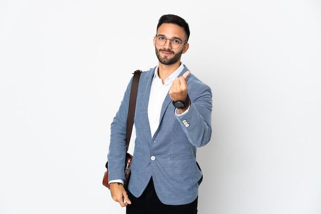 Молодой деловой человек изолирован на белой стене, делая денежный жест
