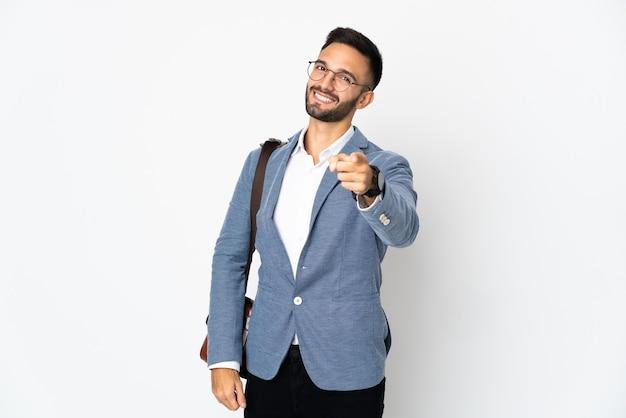 행복 한 표정으로 앞을 가리키는 흰 벽에 고립 된 젊은 사업가
