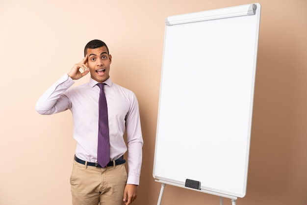 Young business man over isolated wall giving a presentation on white board and intending to realizes the solution