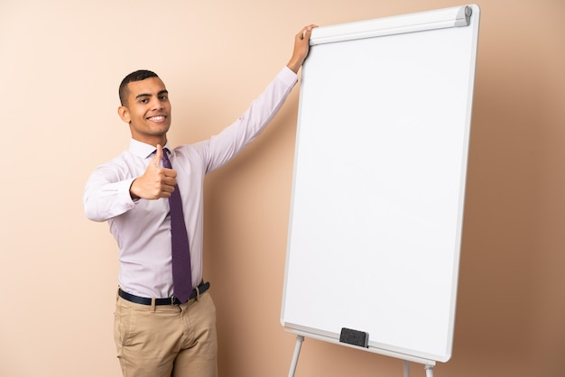 Young business man over isolated wall giving a presentation on white board with thumb up