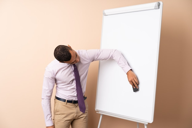 Young business man over isolated wall giving a presentation on white board