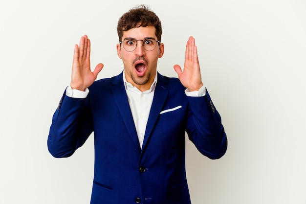 Young business man isolated on white wall surprised and shocked