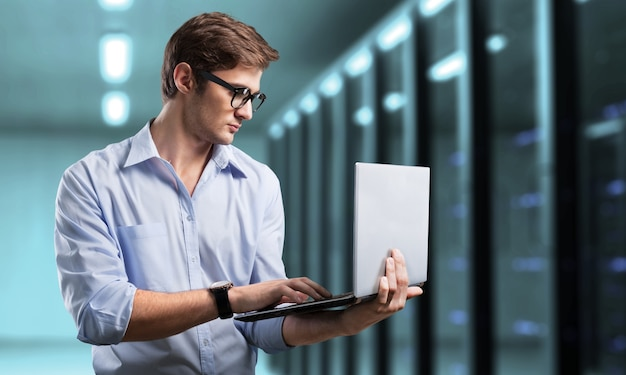 Young business man it engineer with aluminum laptop in server room