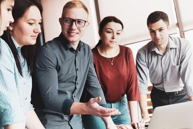 Молодой деловой человек смотрит на своих коллег на совместной встрече и делает жест рукой в сторону компьютера