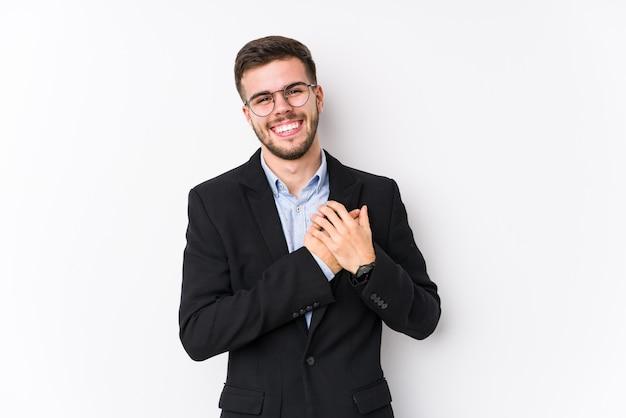 孤立した白い壁でポーズをとって若いビジネスマン心に手を置いて笑っている若いビジネスマン