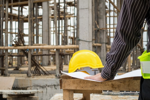 Young business man professional engineer worker at the house building construction site with blueprint