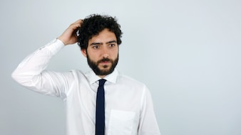 Young business man scratching his head in gesture of doubt