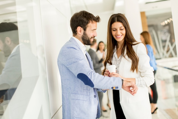 Young business man shows a watch to a businesswoman who drinking coffee