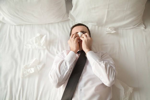 Young business man sick in bed