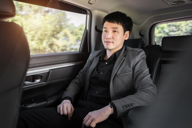 車の後部座席に座っている若いビジネスマン