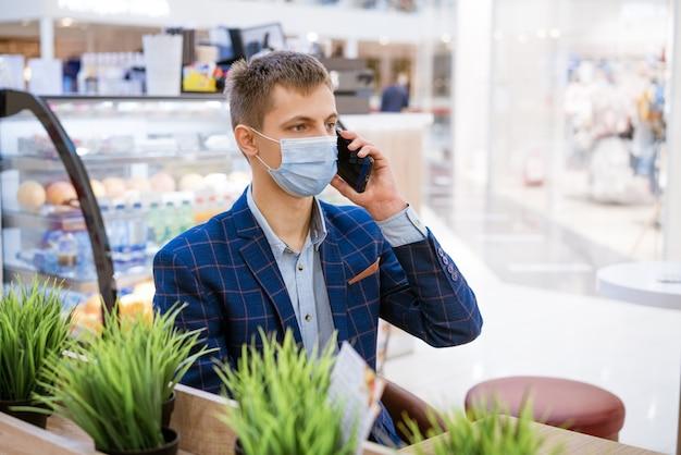 전화로 이야기 카페에서 의료 마스크에 앉아 젊은 비즈니스 남자