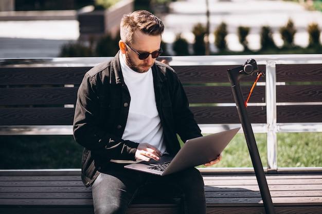 젊은 사업가 벤치에 앉아 컴퓨터에서 작업