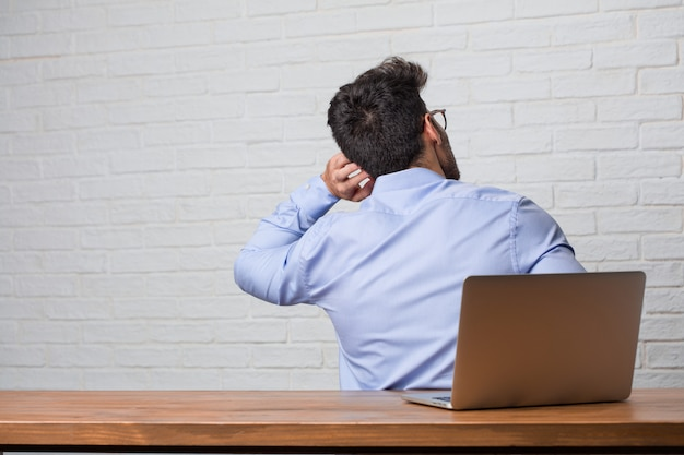 Young business man sitting and working on a laptop showing back, posing and waiting, looking back