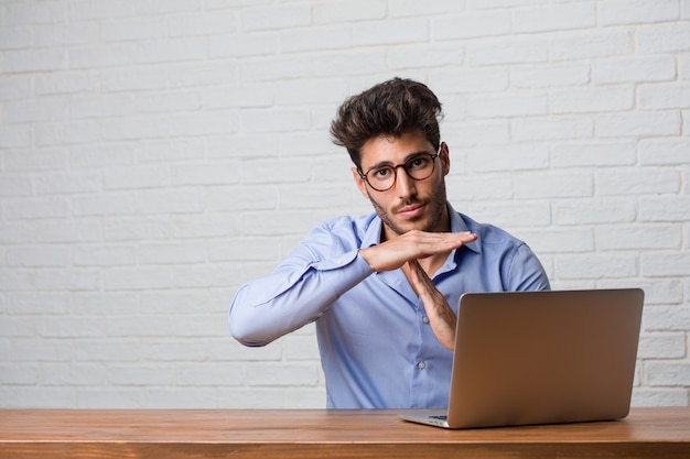Young business man sitting and working on a laptop tired and bored, making a timeout gesture, needs to stop because of work stress, time concept