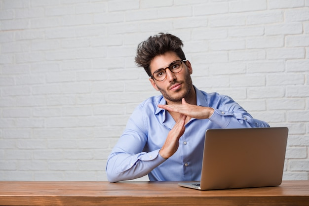 Young business man sitting and working on a laptop tired and bored