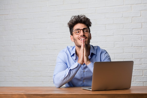 Young business man sitting and working on a laptop very happy and excited