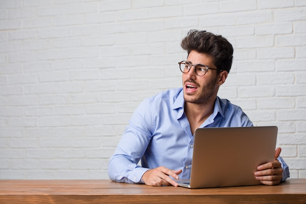 Young business man sitting and working on a laptop very scared and afraid, desperate for something, cries of suffering and open eyes, concept of madness