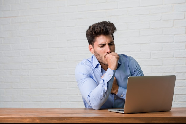 Young business man sitting and working on a laptop with a sore throat, sick due to a virus