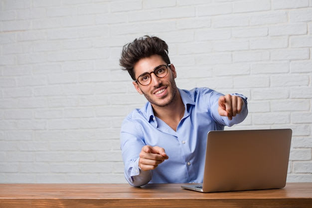 Young business man sitting and working on a laptop